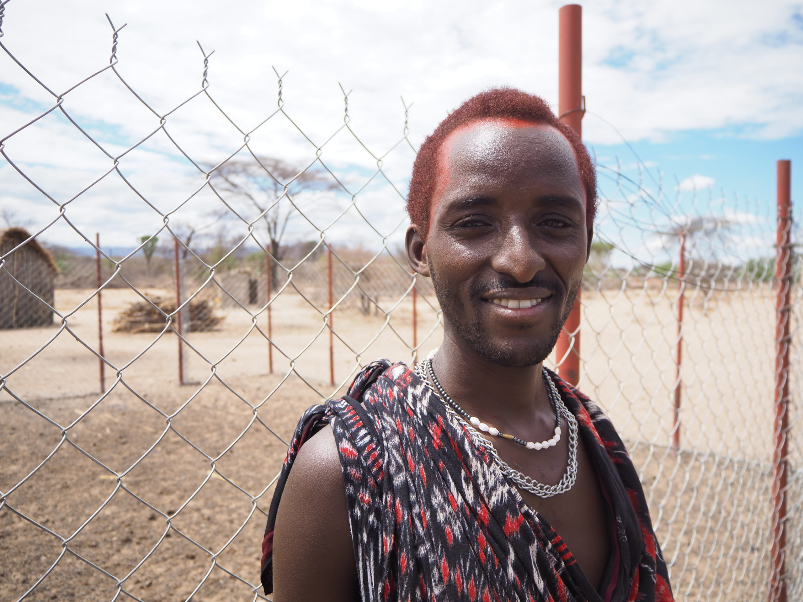 Musse standing by chain-link fence